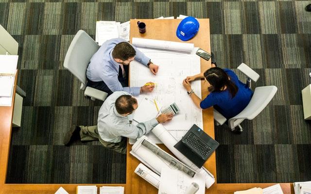 Žena a dvaja muži sediaci pri stole pri pracovnom stretnutí.jpg