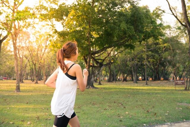 Žena v bielom tričku a čiernych šortkách beží v parku