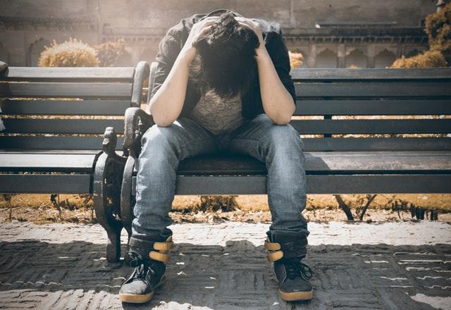 Muž so sklonenou hlavou sedí na čiernej lavičke.jpg