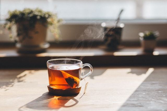 Šálka s vrecúškom čaju položená pri okne.jpg