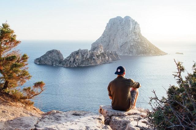 muž sediaci na vrchu skál