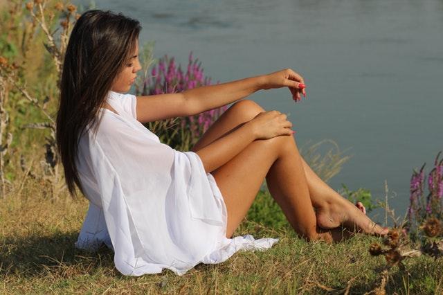 Žena v bielych šatách s odhalenými nohami sedí na brehu jazera