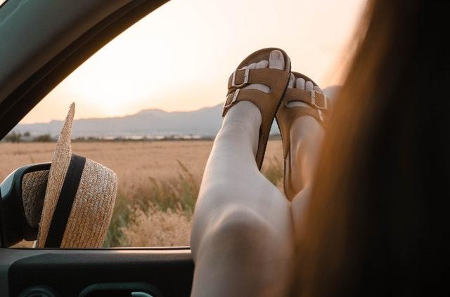 Žena v hnedých šľapkách má vyložené nohy von z okienka auta