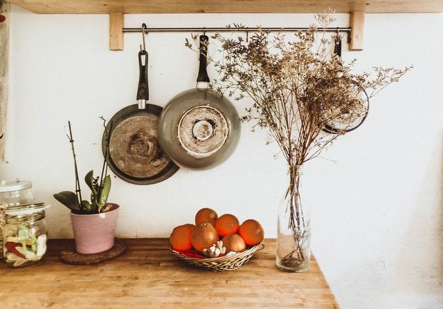 Drevená kuchynská linka, na ktorej sú sušené kvety, nad ňou sú zavesené panvice.jpg